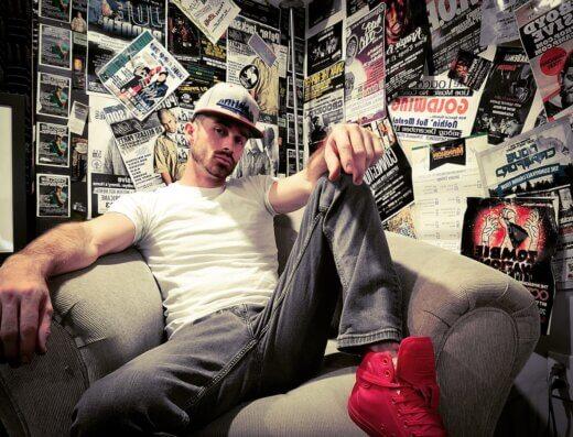 Kingston hip hop artist and producer, Cory Ede (a.k.a. EdeyRoc) poses on a sofa.