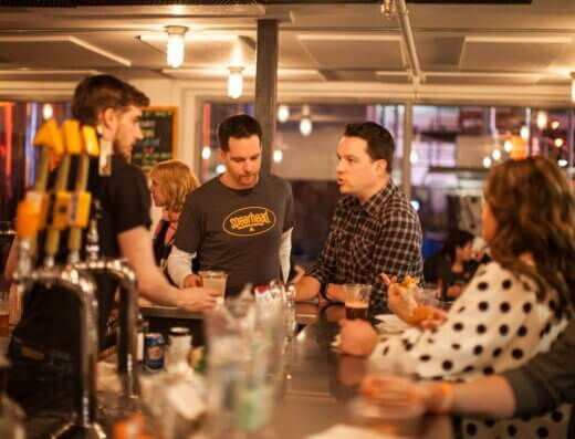 Patrons gather around the bar at Kingston's Spearhead Brewing Co. taproom.