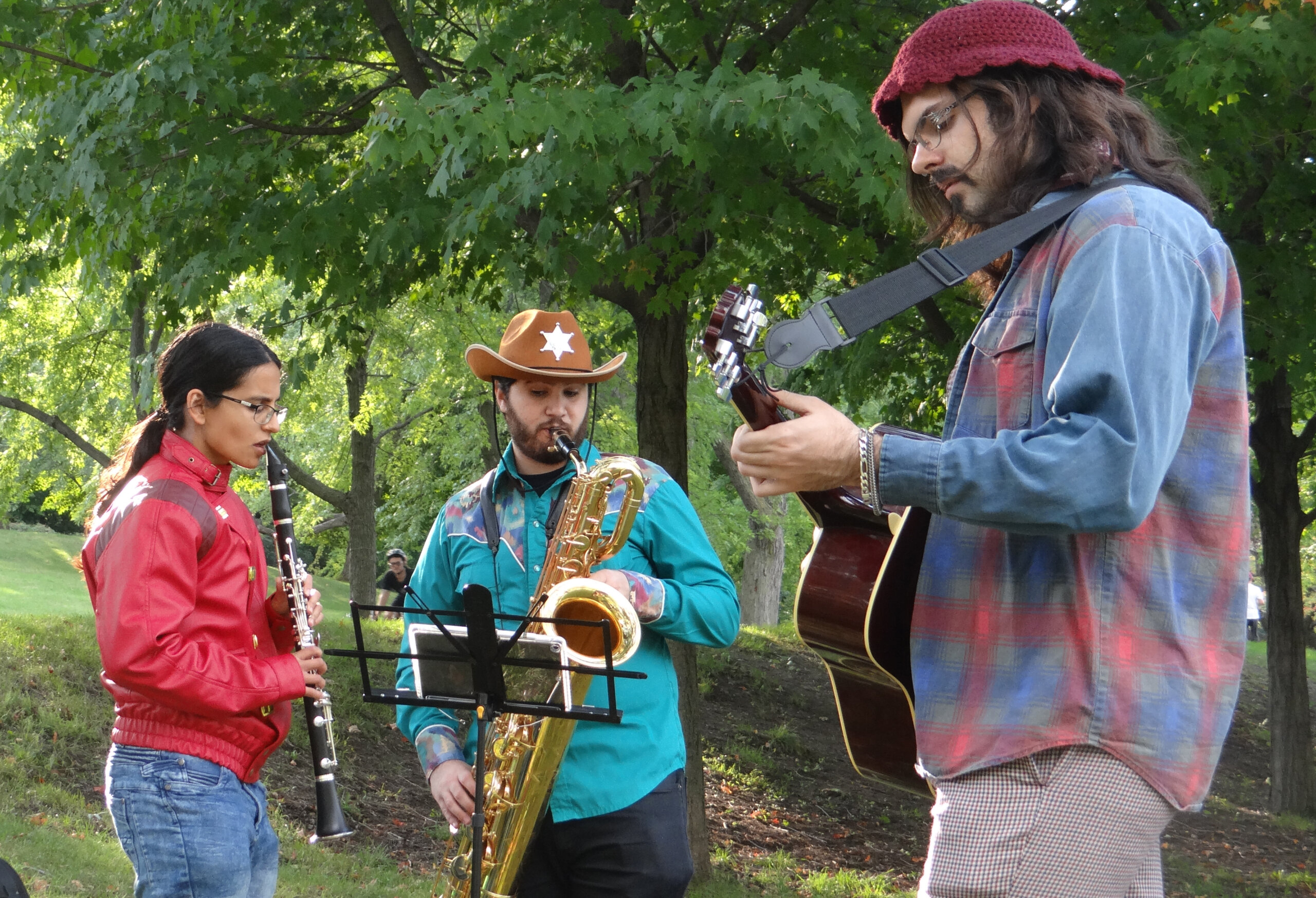 Members of The Maximum Chill play their instruments in an outdoor setting.