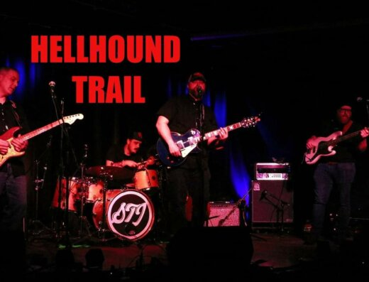 Members of Kingston's Hellhound Trail band play instruments on stage during a live performance.