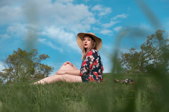 Kingston artist, Erika Lamon, poses outdoors, seated in green grass against a blue sky in warm weather.