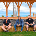 The Kingston Live podcast crew poses with Dan MacKinnon and Ben Vandenberg of MacKinnon Brothers Brewing Co. with bales of hay.